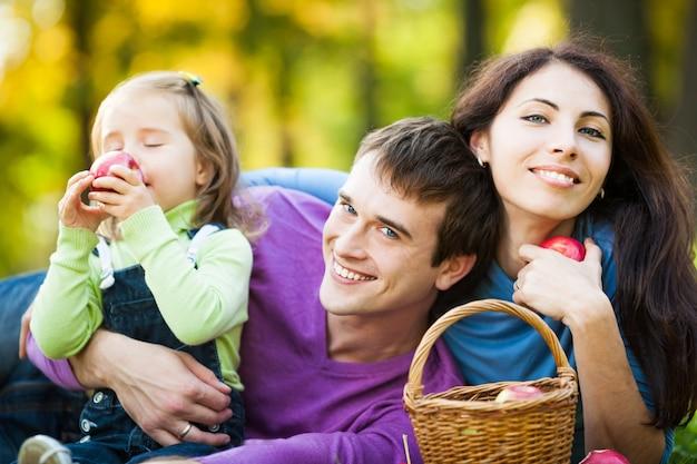 Glückliche familie, die äpfel im herbstpark isst
