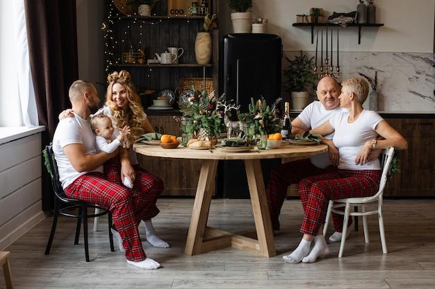 Glückliche familie, die am festlichen tisch am heiligabend sitzt