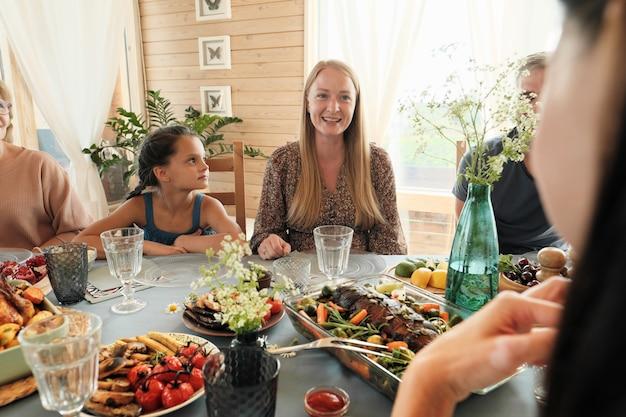 Glückliche familie, die am festlichen tisch sitzt und leckeres essen zu hause isst