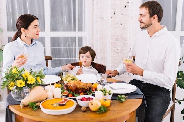 Glückliche familie, die am festlichen tisch trinkt
