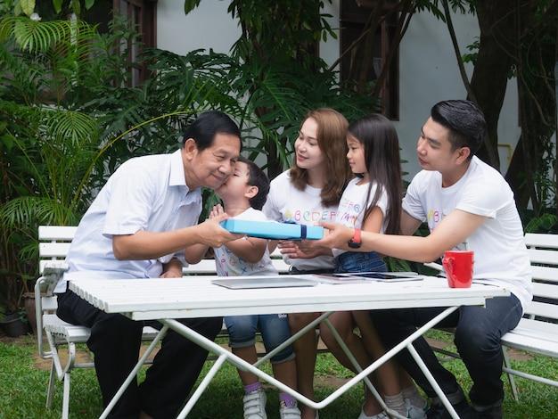 Glückliche familie, die am garten sich entspannt