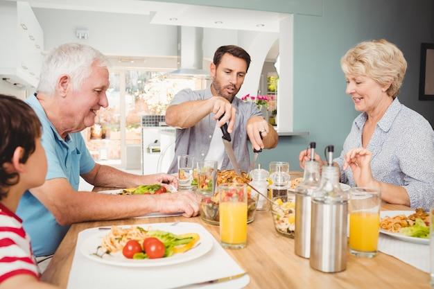Glückliche familie, die am speisetische sitzt