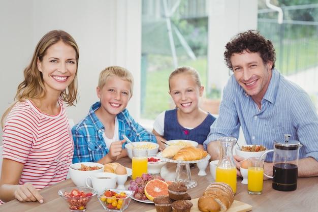 Glückliche familie, die am tisch frühstückt