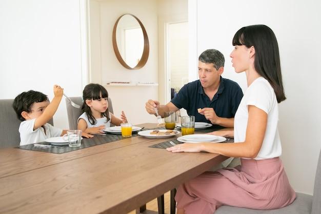 Glückliche familie, die am tisch sitzt und zusammen kekse isst.