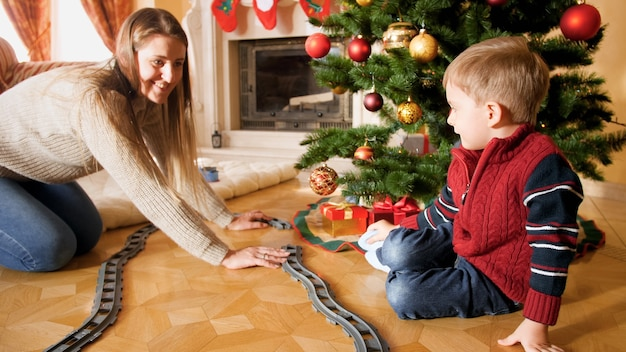 Glückliche familie, die am weihnachtsmorgen mit spielzeugeisenbahn spielt. kind erhält geschenke und spielzeug an neujahr oder weihnachten