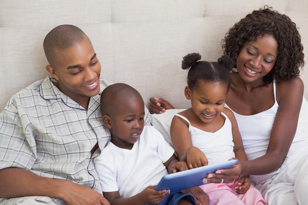 Glückliche familie, die auf bett unter verwendung des tabletten-pc liegt