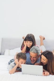 Glückliche familie, die auf bett unter verwendung ihres laptops liegt