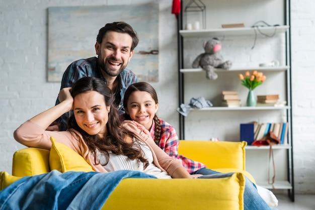 Glückliche familie, die auf couch im wohnzimmer sitzt