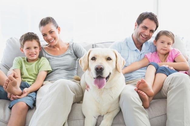 Glückliche familie, die auf couch mit ihrem haustier labrador sitzt