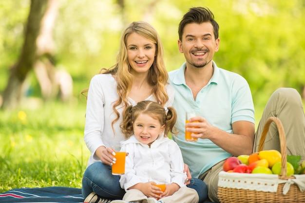 Glückliche familie, die auf dem rasen im park sitzt und saft trinkt.