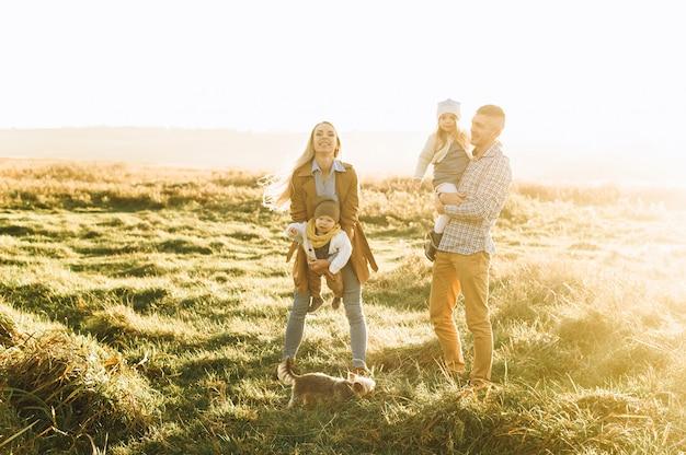 Glückliche familie, die auf der grünen wiese bei sonnenuntergang spielt