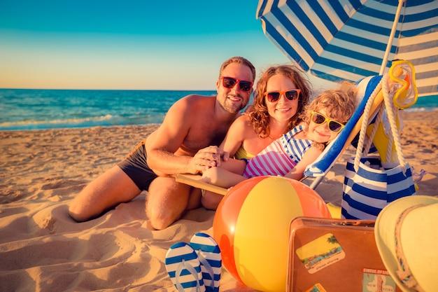 Glückliche familie, die auf der sonnenbank sitzt mann frau und kind, die spaß am strand sommerferienkonzept haben
