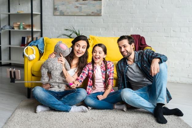 Glückliche familie, die auf einem boden sitzt und ein selfie nimmt