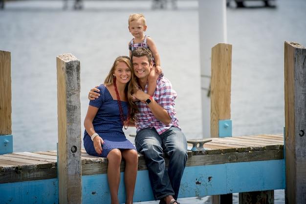 Glückliche familie, die auf einem hölzernen weg mit dem baby auf dem rücken des vaters sitzt