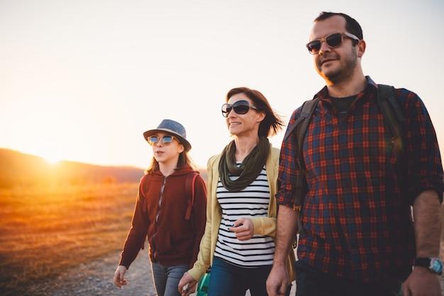 Glückliche familie, die auf einem schotterweg während des sonnenuntergangs wandert