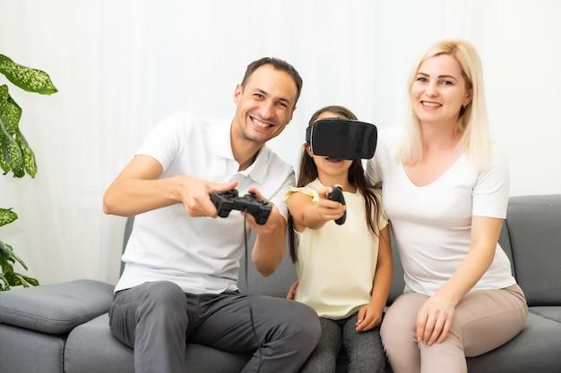 Glückliche familie, die auf einem sofa sitzt und videospiele spielt.