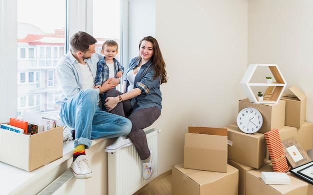 Glückliche familie, die auf fensterbrett mit beweglichen pappschachteln an ihrem neuen haus sitzt
