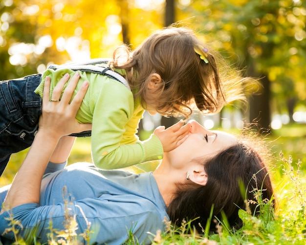 Glückliche familie, die auf gras im herbstpark liegt