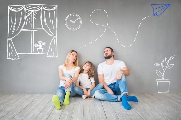 Glückliche familie, die auf holzboden sitzt vater, mutter und kind, die zusammen spaß haben umzugstag