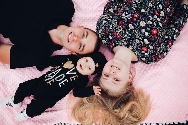 Glückliche familie, die auf rosa decke liegt