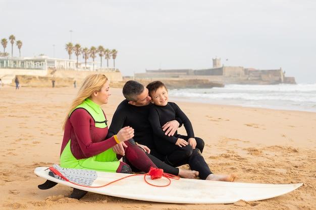 Glückliche familie, die auf sand nahe surfbrett sitzt