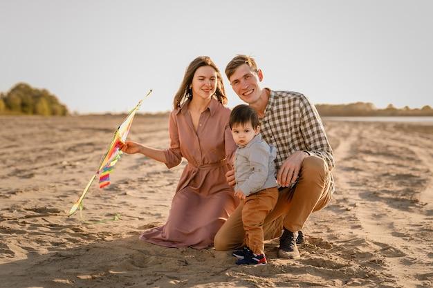 Glückliche familie, die auf sandstrand des flusses geht. vater, mutter hält kleinen sohn auf händen und spielt mit drachen.