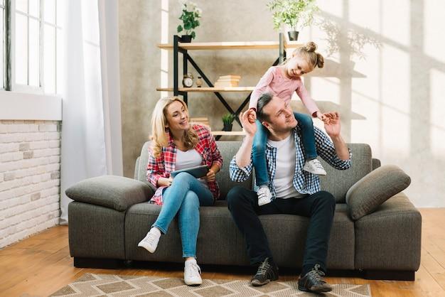 Glückliche familie, die auf sofa im wohnzimmer sitzt