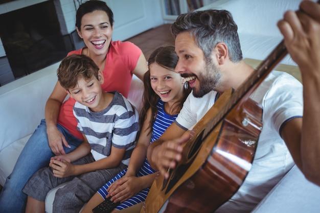 Glückliche familie, die auf sofa mit einer gitarre sitzt