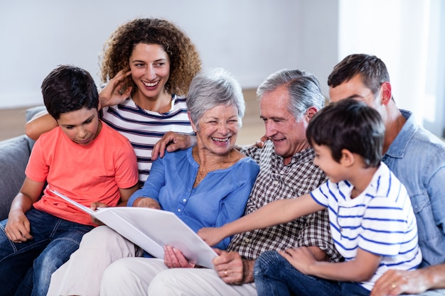 Glückliche familie, die auf sofa sitzt und fotoalbum betrachtet