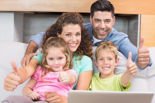 Glückliche familie, die auf sofa unter verwendung des laptops aufgibt daumen sitzt