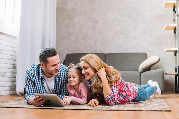 Glückliche familie, die auf teppich unter verwendung der digitalen tablette liegt