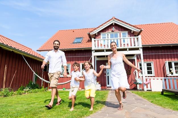Glückliche familie, die auf wiese vor haus auf vorgartengras läuft