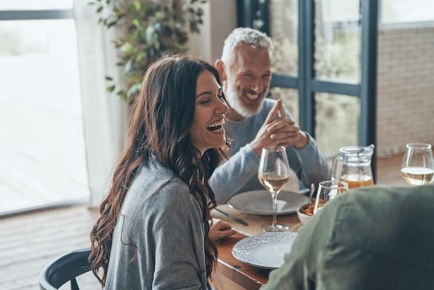 Glückliche familie, die beim gemeinsamen abendessen kommuniziert und lächelt smiling