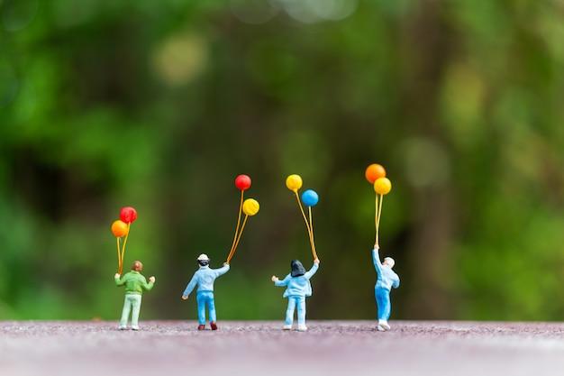 Glückliche familie, die bunte ballone hält