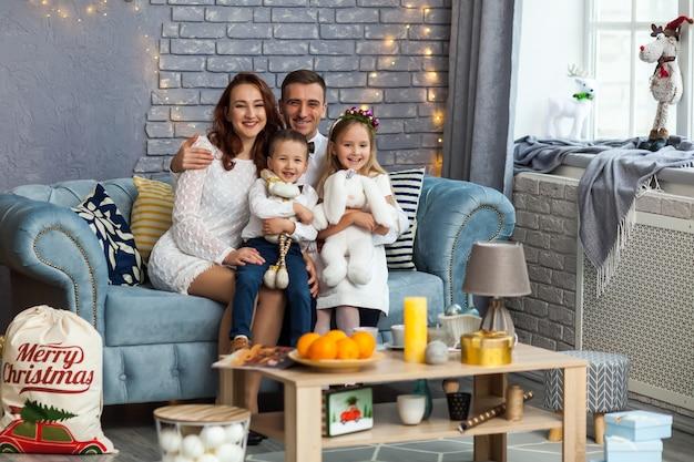 Glückliche familie, die das weihnachtsgeschenk betrachtet kamera hält