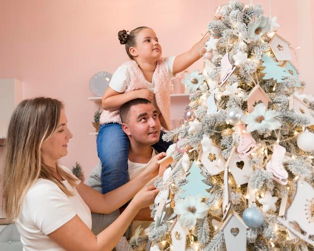 Glückliche familie, die den weihnachtsbaum verziert