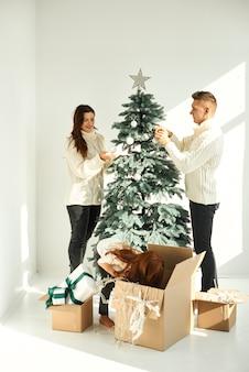 Glückliche familie, die den weihnachtsbaum zu hause verziert