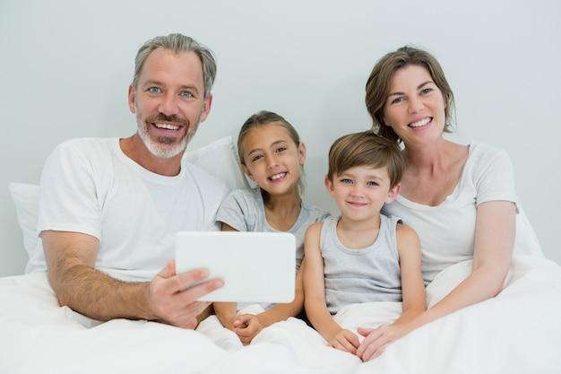 Glückliche familie, die digitales tablett auf bett im schlafzimmer zu hause verwendet