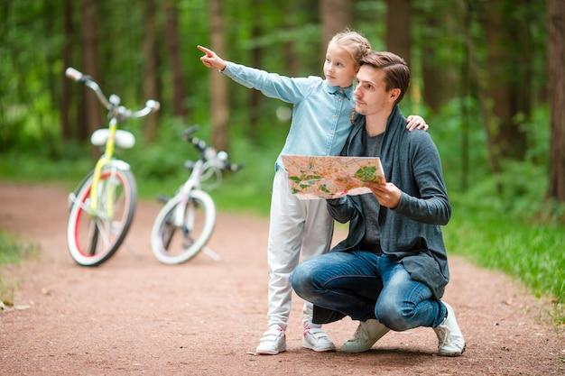 Glückliche familie, die draußen am park radfährt