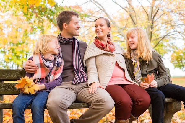 Glückliche familie, die draußen auf bank im herbst sitzt