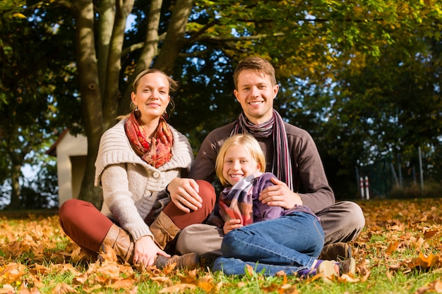 Glückliche familie, die draußen auf gras im herbst sitzt