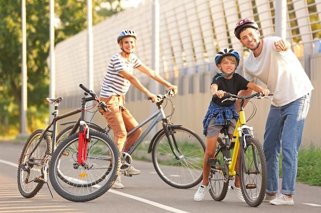 Glückliche familie, die draußen fahrrad fährt