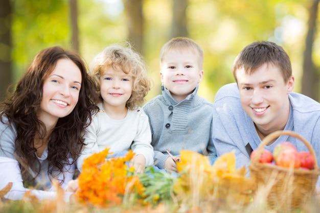 Glückliche familie, die draußen im herbstpark gegen unscharfen blätterhintergrund picknickt