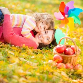Glückliche familie, die draußen im herbstpark spielt