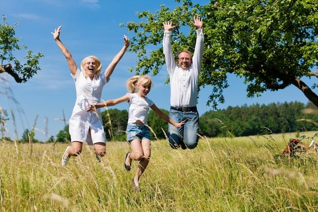 Glückliche familie, die draußen in die sonne springt