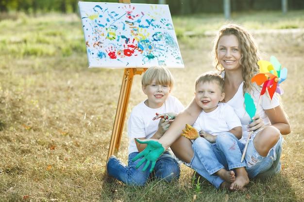 Glückliche familie, die draußen zeichnet. junge mutter, die spaß mit ihren kleinen kindern hat