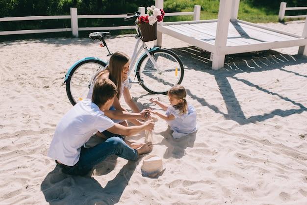 Glückliche familie, die draußen zeit zusammen verbringt. vater, mutter und tochter haben spaß und laufen