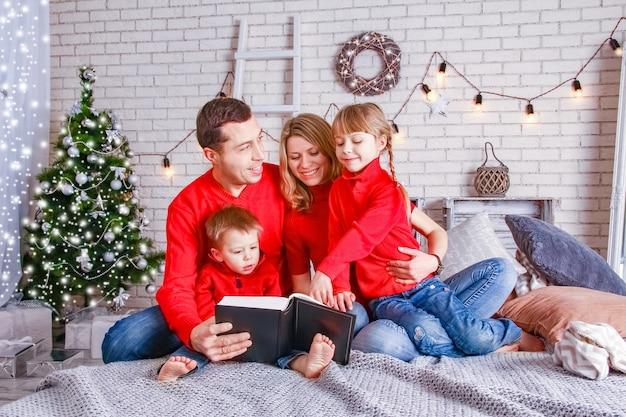 Glückliche familie, die ein buch zu hause zu weihnachten liest