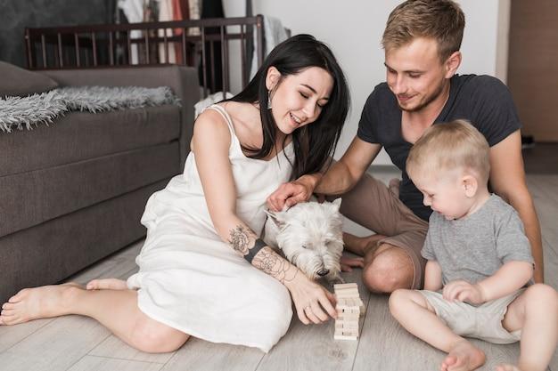 Glückliche familie, die ein hölzernes turmspiel der blöcke mit hund spielt