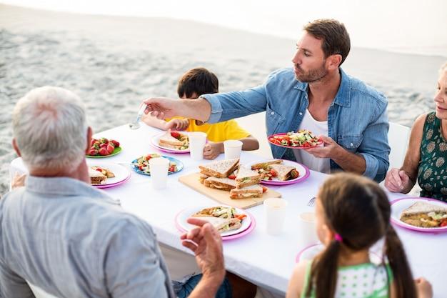Glückliche familie, die ein picknick am strand hat
